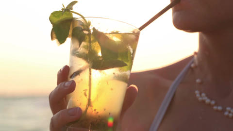 Woman enjoying a tropical mojito cocktail Stock Video Footage