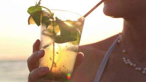 Woman enjoying a tropical mojito cocktail Footage