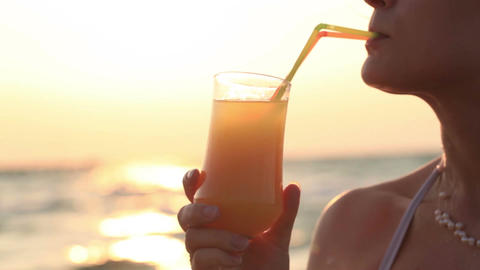 Woman sipping a refreshing cocktail at sunset Stock Video Footage