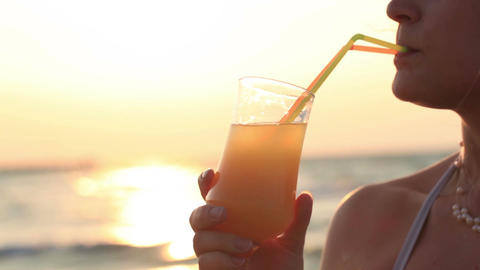Woman sipping a refreshing cocktail at sunset Footage