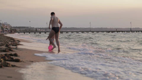 Father and son running along the beach with ball Stock Video Footage