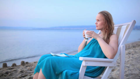 Woman enjoying a cup of tea at the seaside Stock Video Footage