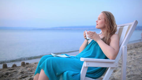 Woman enjoying a cup of tea at the seaside Footage