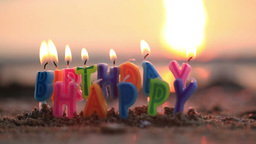 Birthday candles burning on a seashore Footage