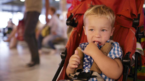 Young Boy Sitting In A Child Trolley In An Airport stock footage