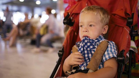 Young boy sitting in a child trolley in an airport Stock Video Footage