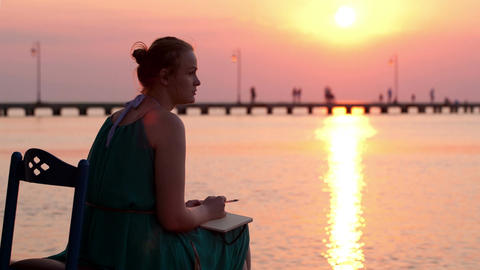 Young woman writing in her diary by the seashore Stock Video Footage