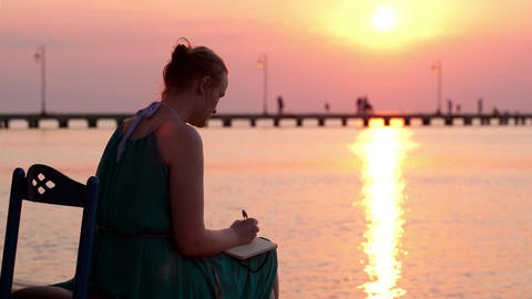 Young woman writing in her diary by the seashore Footage