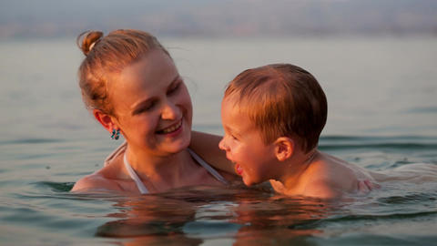 Mother playing with her young son in the beach Stock Video Footage