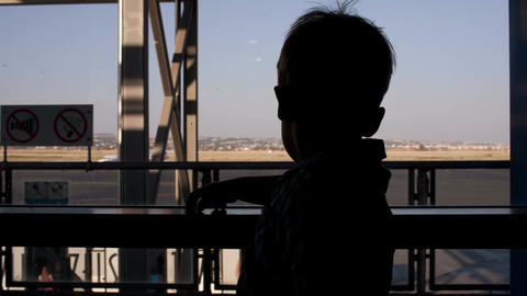 Young boy looking through window in the airport Stock Video Footage