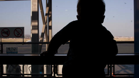 Young Boy Looking Through Window In The Airport stock footage
