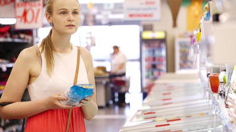 Young woman buying products at the supermarket Stock Video Footage