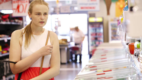Young woman buying products at the supermarket Footage