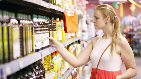 Young woman buying olive oil Stock Video Footage
