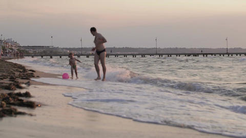 Father and son running along the beach with ball Footage