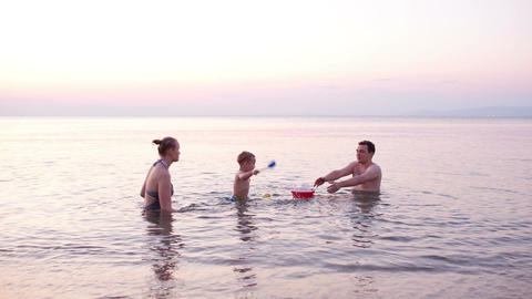 Young family playing red toy boat at sunset Stock Video Footage