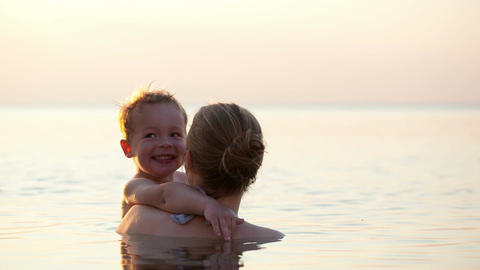 Loving mother hugging with her son in the sea Stock Video Footage