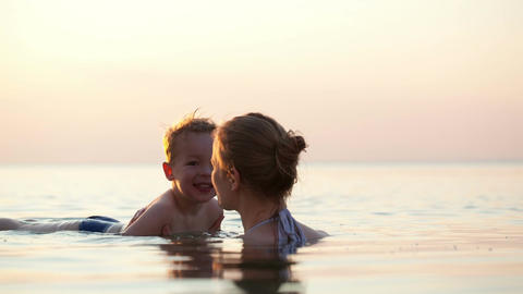 Young mother teaches her little son to swim Stock Video Footage