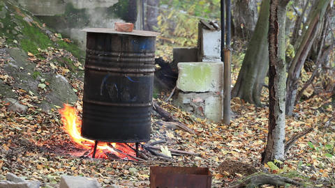 cooking fish smoking in a barrel Stock Video Footage