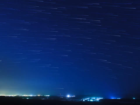 Stars leave traces above the city. Time Lapse Footage