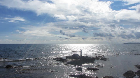 fisherman with spinning near sea in sunlight Stock Video Footage