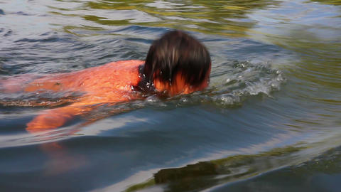 teenager boy swimming in river Stock Video Footage