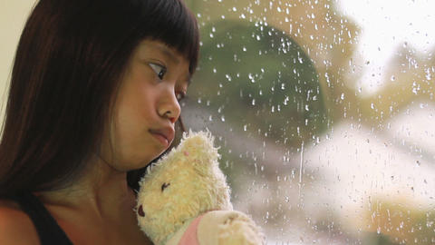 Sad Asian Girl Kisses Teddy Bear By Window Footage