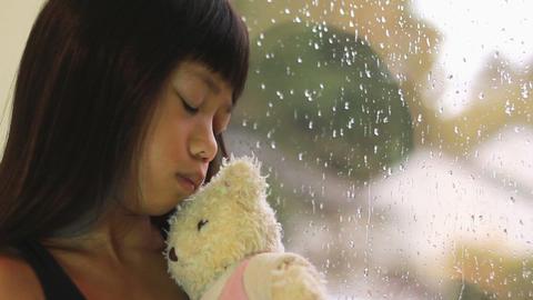 Sad Asian Girl Kisses Teddy Bear By Window Stock Video Footage