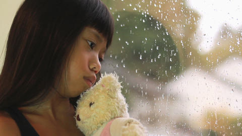 Sad Asian Girl Kisses Teddy Bear By Window Stock Video Footage
