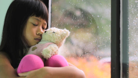 Sad Little Girl Sits By Window On Rainy Day Stock Video Footage