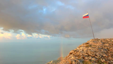 Russian flag on the top of a mountain on the backg Footage