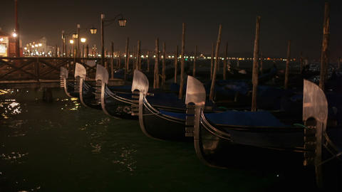 Venetian gondolas tied near the pier at night on S Stock Video Footage