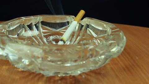 Smoking cigarette in ashtray dolly shot front view Footage