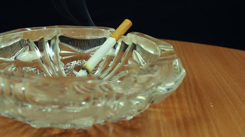 Smoking cigarette in ashtray dolly shot front view Stock Video Footage