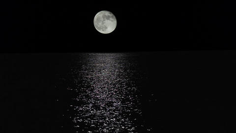 Moonlight path with low fool moon above the sea Stock Video Footage
