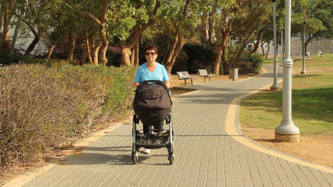 woman walking with a baby in a stroller Stock Video Footage