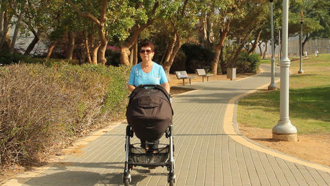 woman walking with a baby in a stroller Footage