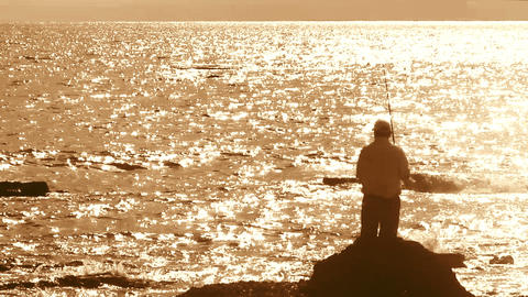 Fisherman With Spinning Silhouette At Sea Sunset stock footage
