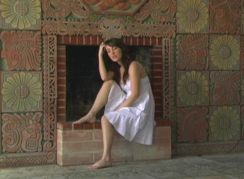 Beautiful Girl Sitting at a Fireplace (1) Stock Video Footage