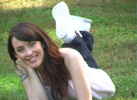 Beautiful Brunette Lying in the Grass (1) Stock Video Footage