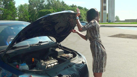 Brunette opens the hood of a car Footage