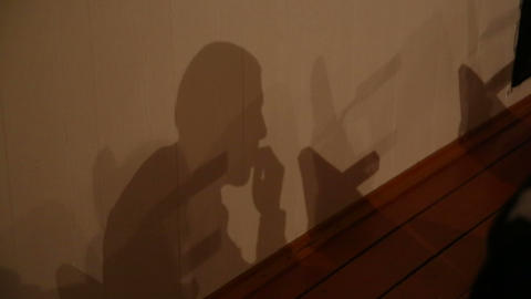 Shadow on the wall of the sitting man Stock Video Footage