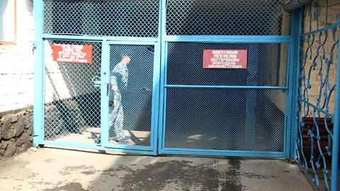 The guard passes through the gates of the prison Stock Video Footage