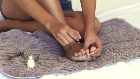 A young woman painting her toe nails Footage