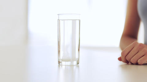 woman dissolving a pill in glass of water Stock Video Footage