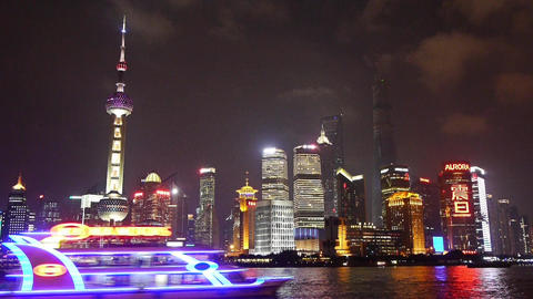 Brightly lit ship passing Shanghai bund at night,Lujiazui business building Animation