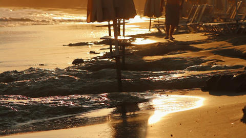A man walking along the beach at sunset Stock Video Footage
