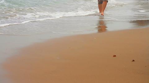 Man walking barefoot on the beach Stock Video Footage
