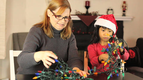 Girls Untangling Christmas Lights Stock Video Footage