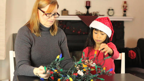 Mother And Daughter Untangling Christmas Lights Stock Video Footage